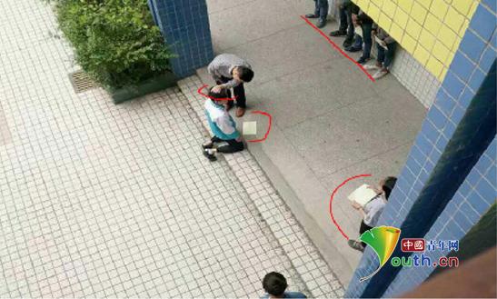 图片显示,张姓老师揪住跪在地上的学生的头发,学生面前还有一排学生靠墙站着,侧面也有学生站着。