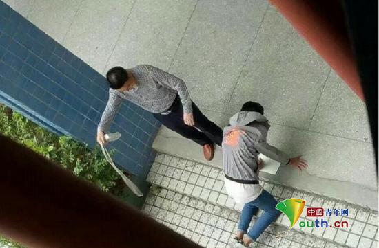 张姓老师手拿带插线板的电线殴打跪在地上的学生。